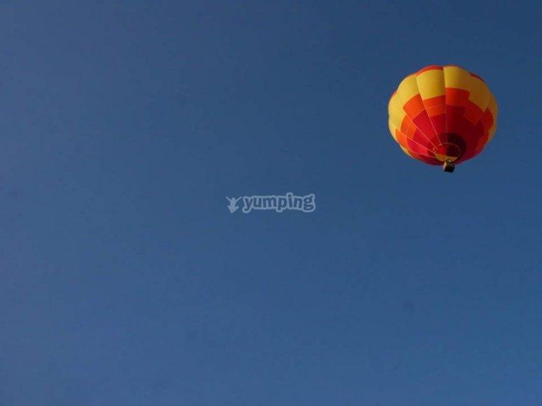 Volando en el cielo azul con el globo