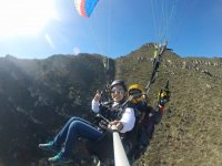 Saluting to the camera from the paraglider