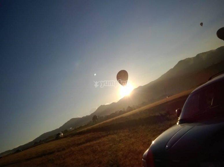 Globo volando con la salida del sol