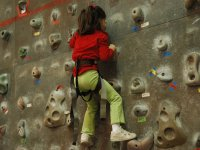Little ones on the rock wall with a red sweatshirt