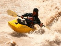 Surfing the rapids in the kayak