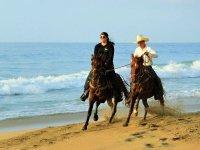 Cabalga por la orilla de la playa