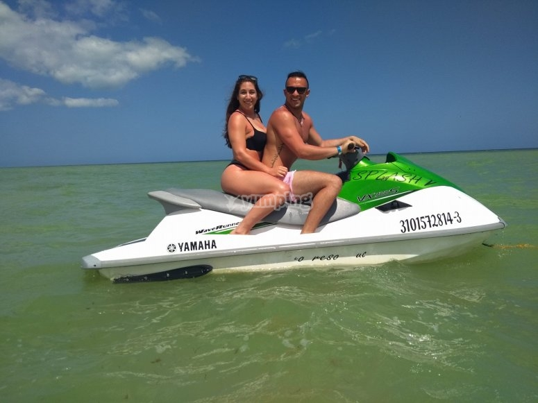 Couple ride a jet ski