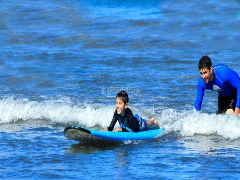 Niño aprendiendo a surfear junto al monitor