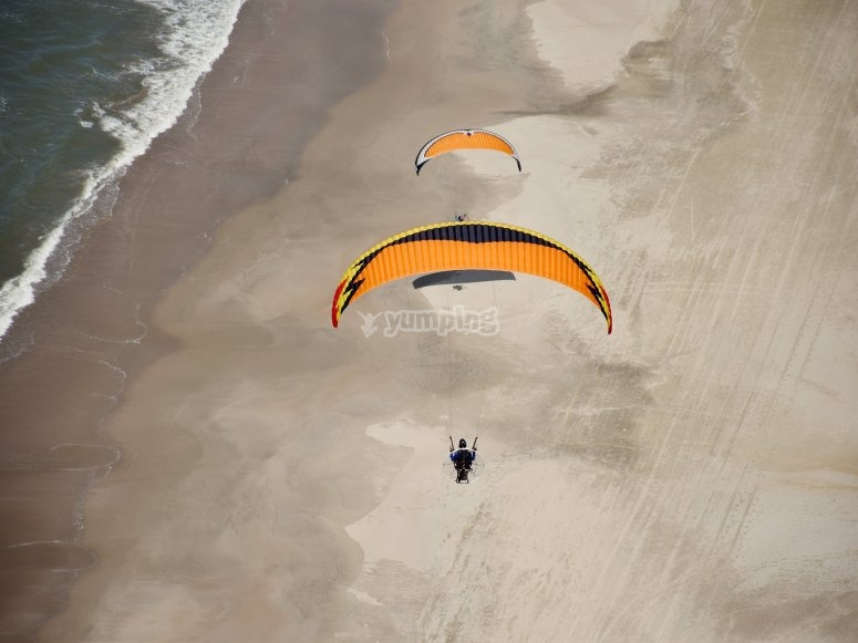 Fly over the beach in paramotor