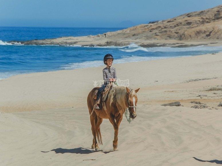 Niño en la playa a caballo