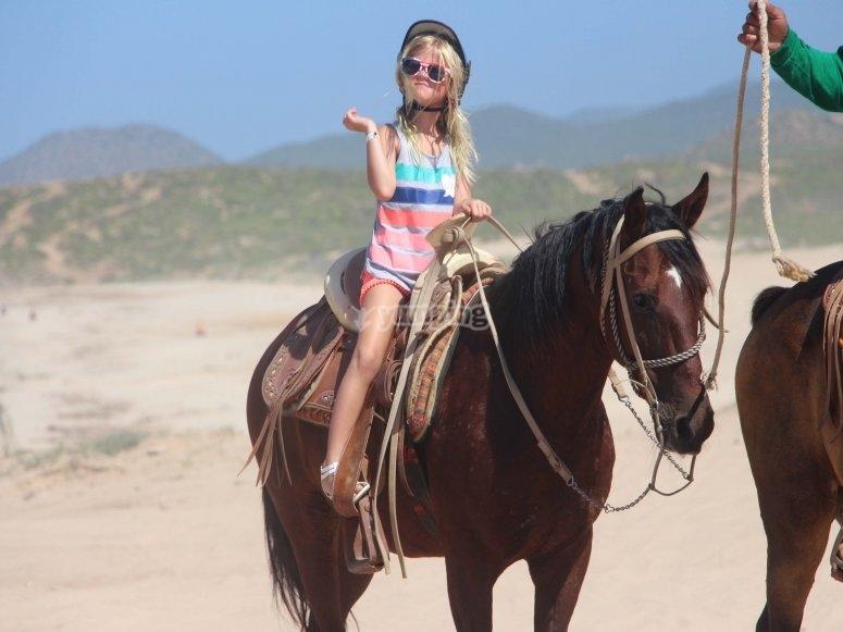 Niña emocionada en caballo