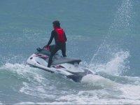 De pie con casco en la moto de agua